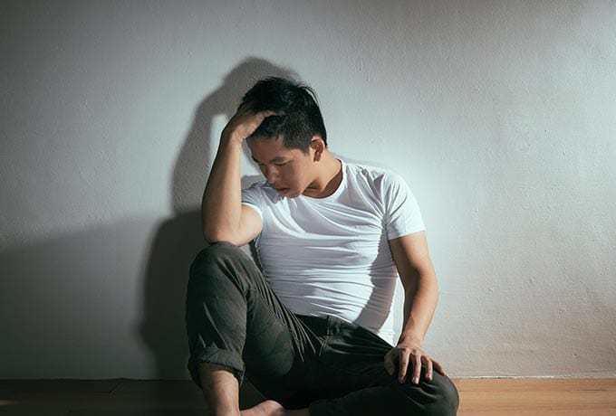 Self-harm: Man sitting on the floor