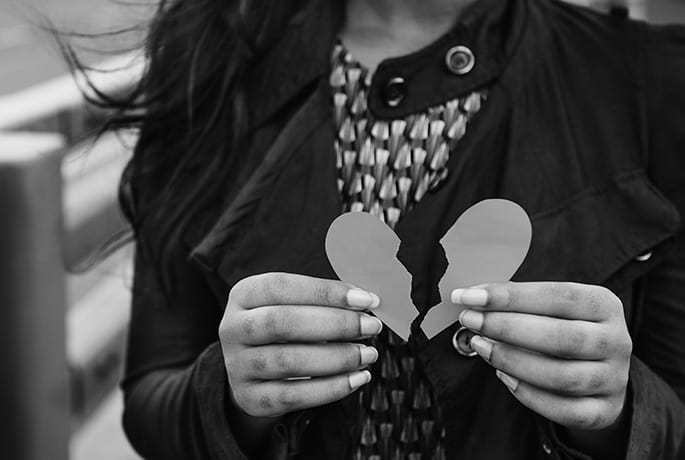 Women holding a piece of card in the shape of a broken heart