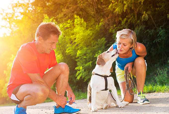 Self care looking after yourself couple going for a run with their pet dog