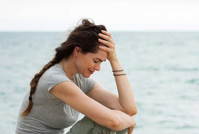 Women sat crying at the beach showing suicide warning signs