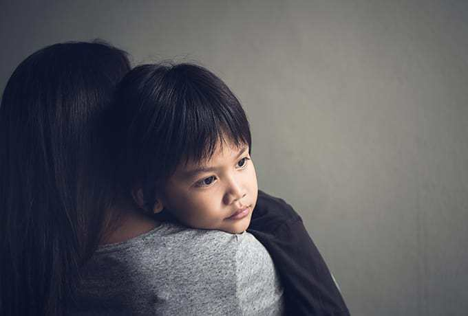 Supporting Children: Child being held by his mother after a suicide