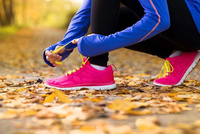 A woman tying laces on her running shoes