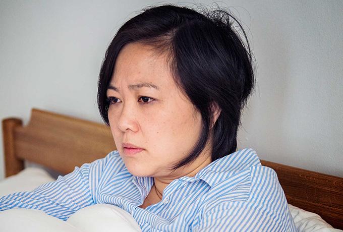 Women in bed suffering from depressed symptoms
