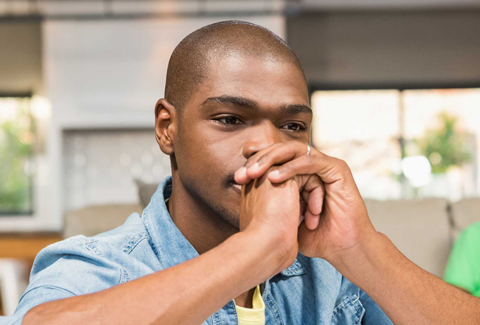 Man sat asking himself what are the causes of anxiety