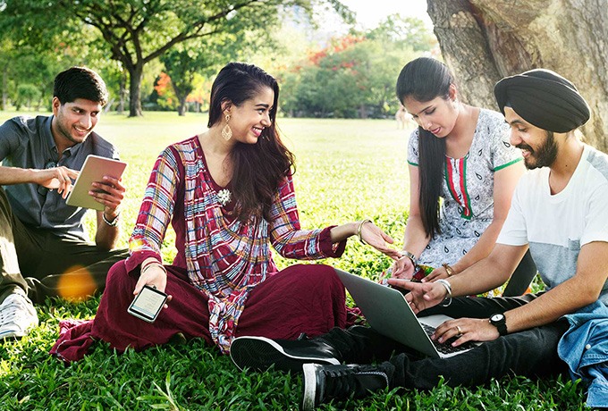 People sat in park having fun - Loneliness and social relationships tips