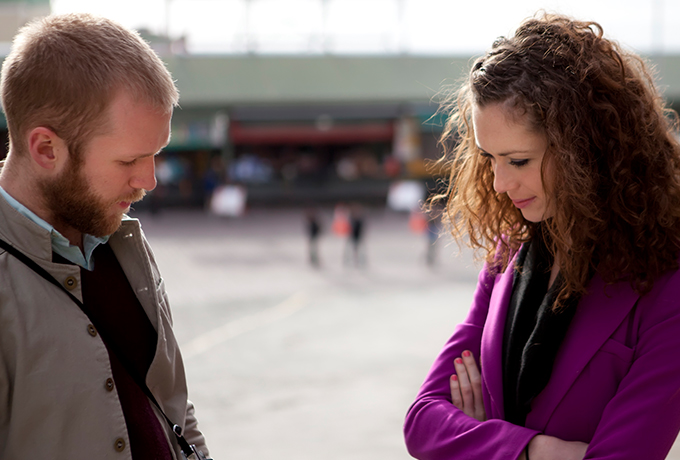 Two people standing opposite one another talking about suicide