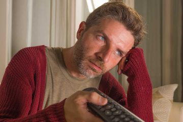 Man anxious and stressed watching tv