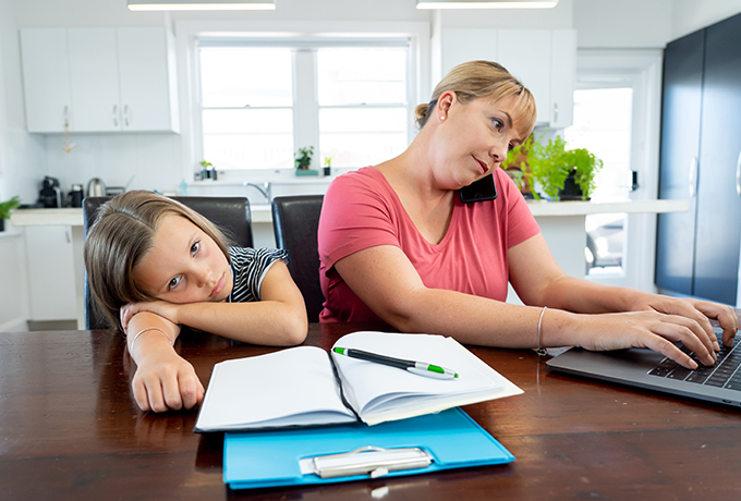 Young mother and daughter working from home