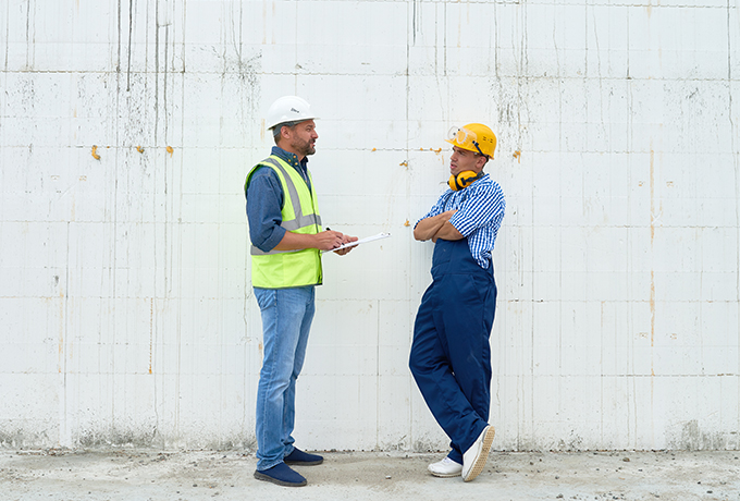 two work colleagues talking on a building site