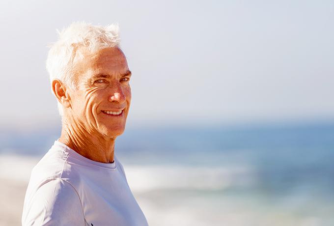 Man walking along a beach smiling