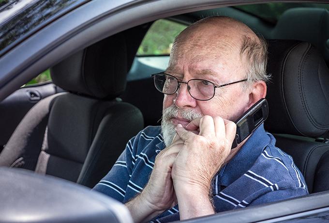 Elderly worried man sat in a car talking on a phone