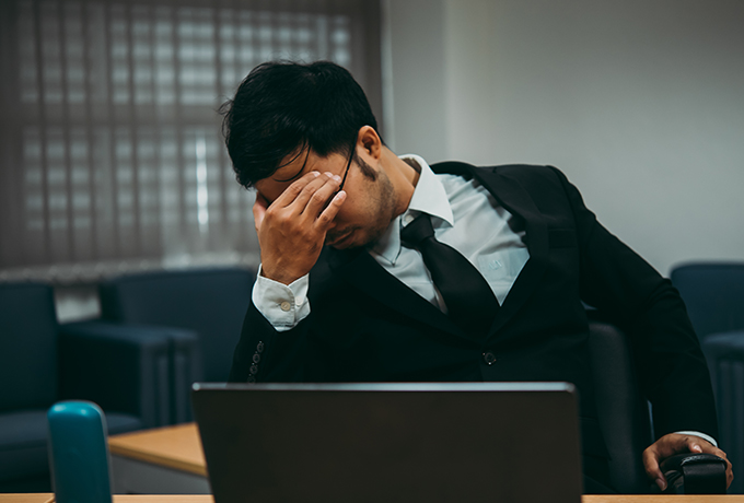 A man clearly stressed sat at a desk at work